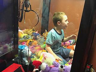 为抓娃娃男孩钻娃娃机被困