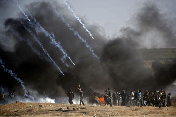 8 5月14日,在加沙地带与以色列接壤的边境地区,巴勒斯坦抗议者在示威活动中躲避以军的催泪弹。(新华 法新)