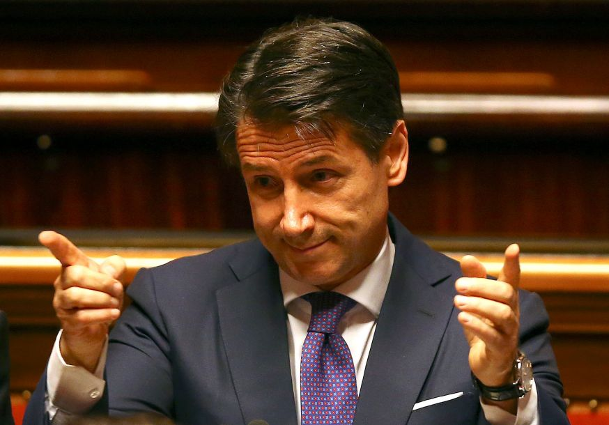 """孔特对参议员说:""""我们将强烈呼吁修改《都柏林公约》,以获得各方对公平分配责任的尊重,并实现一个针对寻求避难者的强制性自动分配体系。""""根据该公约,难民必须在其进入的第一个欧盟成员国申请避难,这意味着意大利要应对数量庞大的难民。孔特的首次政策演说重申了执政联盟几个关键的宣言性议题,包括对移民采取强硬立场、拒绝财政紧缩政策,以及对莫斯科采取和解姿态。孔特说:""""我们将推动对制裁体系进行一次评估。""""(图片来源:法新社)"""