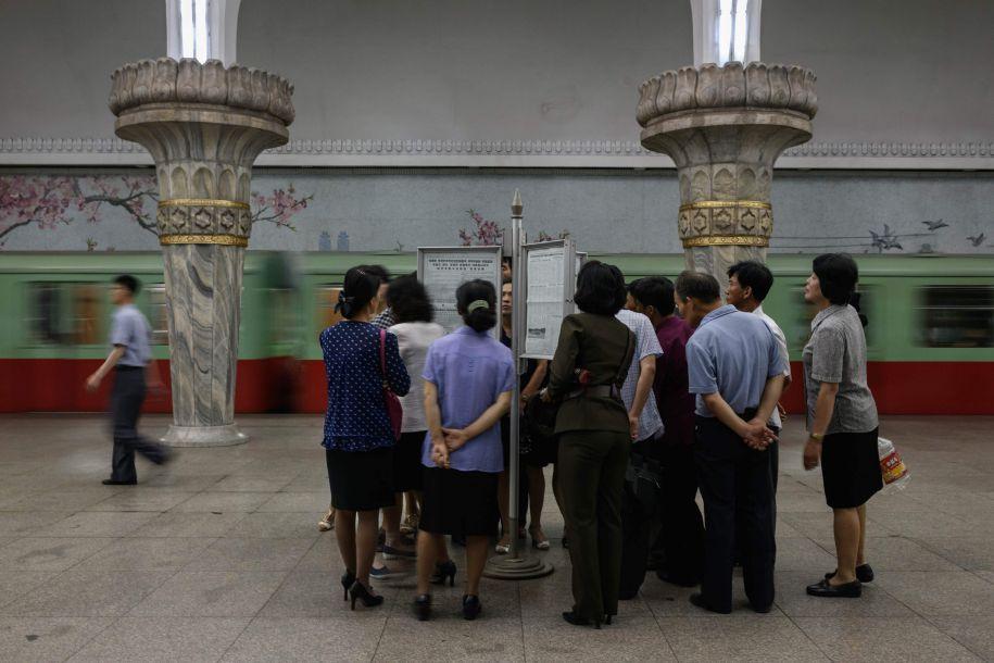6月13日,朝鲜平壤,朝鲜民众在地铁站中阅读有关朝美首脑会晤的报纸。(图片来源:法新社)