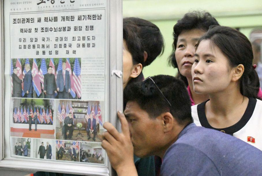 6月13日,朝鲜平壤,朝鲜民众在地铁站中阅读有关朝美首脑会晤的当地报纸。报道称,朝鲜民众密切关注朝鲜最高领导人金正恩与美国总统特朗普在新加坡会晤的消息。(图片来源:法新社)17