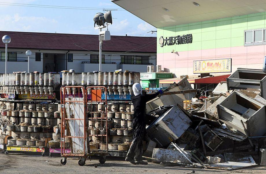 7月10日,在日本冈山县仓敷市真備町一家超市前,工作人员在整理浸过水的货物。日本西部地区连降特大暴雨,引发30多年来最严重水灾。截至10日晚,日本全国因暴雨致死人数已上升至158人,另有57人下落不明。新华社记者马平摄