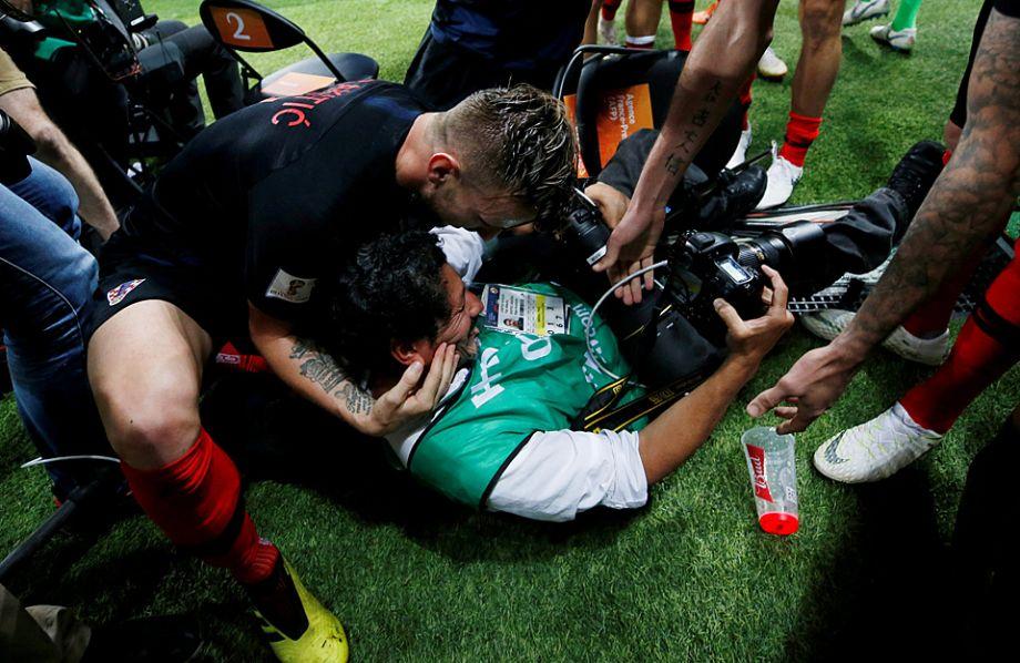 当天坐在椅子上的是来自萨尔瓦多的法新社摄影记者尤里·柯蒂斯。全世界的观众都看到,狂喜的克罗地亚球员冲到了他那一边,互相扑在彼此身上的时候,把柯蒂斯也扑倒了。