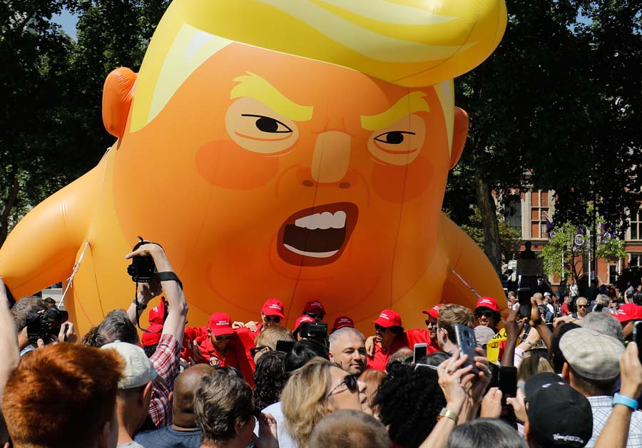 """7月13日,抗议者在英国议会大厦附近,将一个巨大的""""特朗普宝宝""""的充气气球放飞升空,以抗议特朗普对英国争议性的访问。14"""