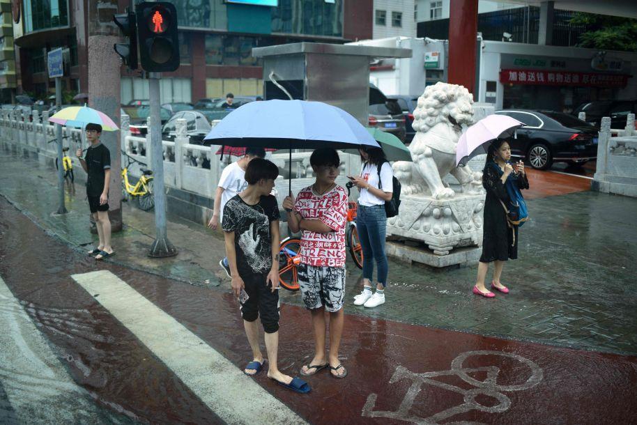 7月17日,中国北京,一群撑着雨伞的行人在雨天过马路。(图片来源:法新社)