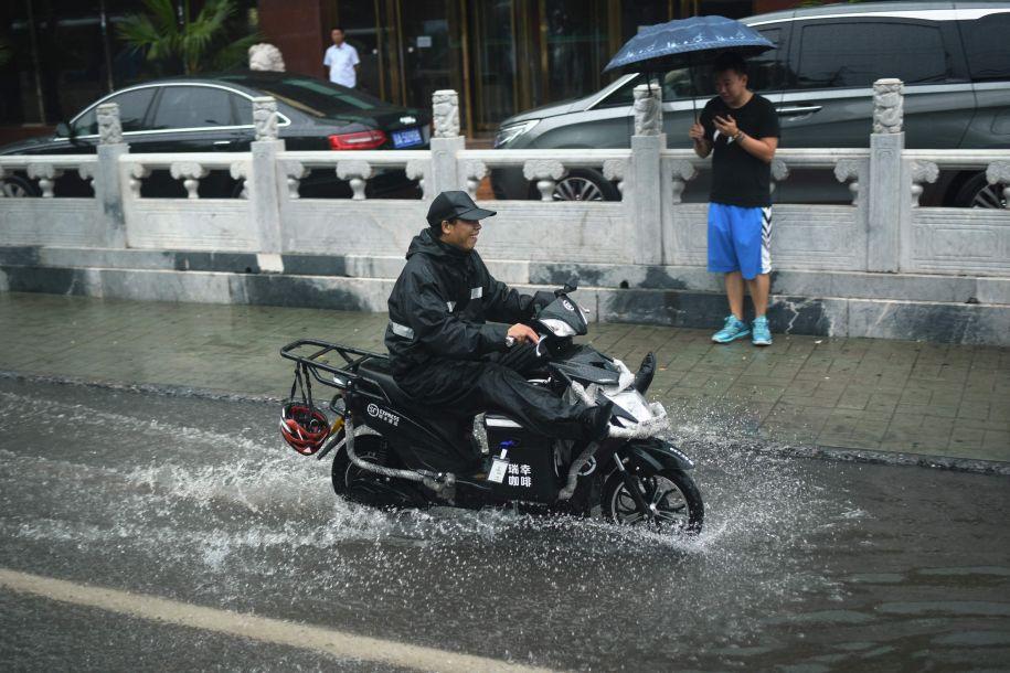 据法新社报道,从7月15日夜间开始,中国北京及周边地区持续迎来大到暴雨,北京市气象台等部门接连发布暴雨预警信号,提醒市民注意防雨和交通安全。图为一名快递员从北京市区一段积水的路面骑过。(图片来源:法新社)