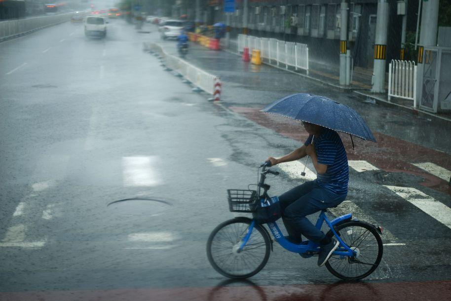 7月17日,中国北京,一名手里拿着伞的男子在街上骑着一辆共享自行车。(图片来源:法新社)