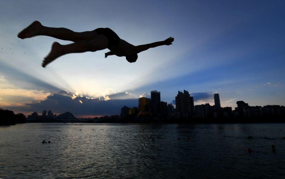 一江碧水享清凉:广西柳州连续发布高温橙色预警 市民戏水消暑