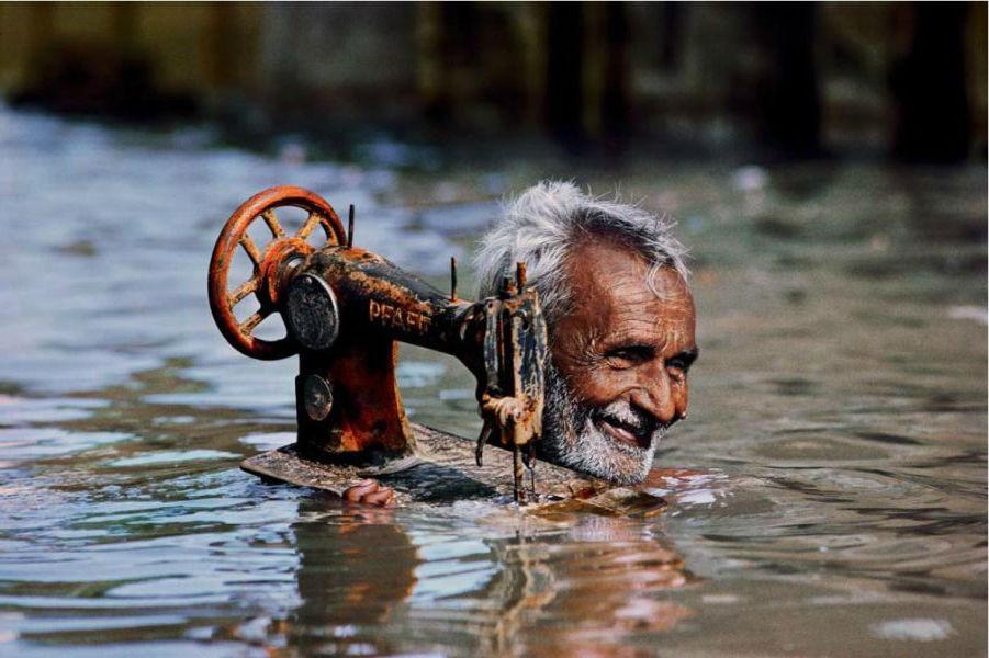 古吉拉特邦博尔本德尔一位老人将缝纫机举起涉水而过