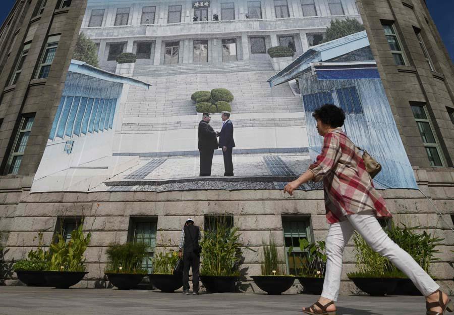 """当地时间2018-09-25,韩国首尔,市政厅挂起巨幅韩国总统文在寅和朝鲜最高领导人金正恩握手的海报。韩朝首脑会谈将于9月18日到20日在平壤举行。据韩媒报道,第三次""""文金会""""也将讨论半岛西部海域和平区问题。32"""