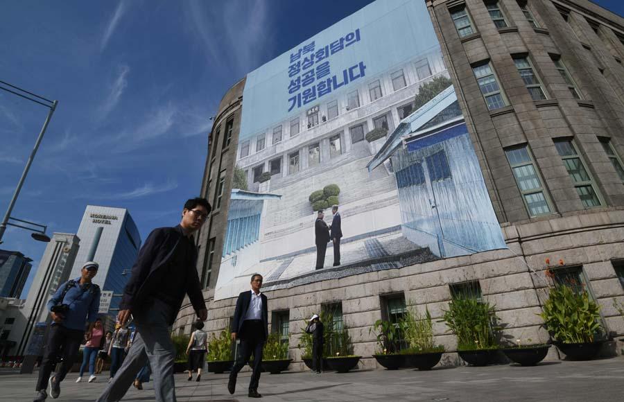 """当地时间2018-09-25,韩国首尔,市政厅挂起巨幅韩国总统文在寅和朝鲜领导人金正恩握手的海报。韩朝首脑会谈将于9月18日到20日在平壤举行。据韩媒报道,第三次""""文金会""""也将讨论半岛西部海域和平区问题。"""