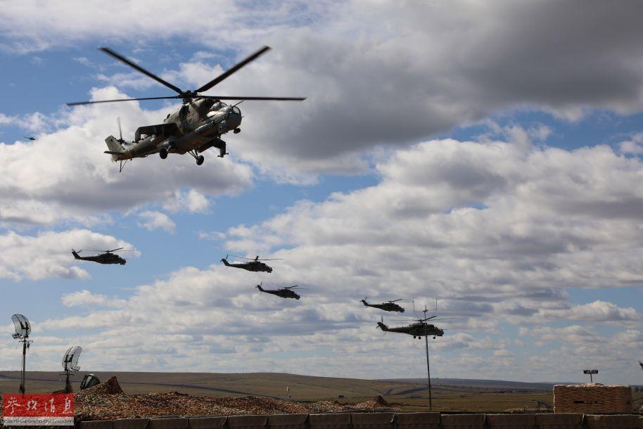 """9月11日至13日,号称俄罗斯史上最大规模的""""东方-2018""""联合军演在俄罗斯楚戈尔草原举行。俄军参演兵力达到30万人,参演各型军机1000多架,地面参演坦克及装甲车辆达3.6万辆。首次受邀参演的中方部队参演兵力3200人,地面装甲车辆1000余辆,战机及直升机30架。图为""""东方-2018""""战略演习联合战役实兵演练开始后,俄方米-24武直机群进入演习地域,开始实施机动防御。(新华社记者 樊永强摄)17"""