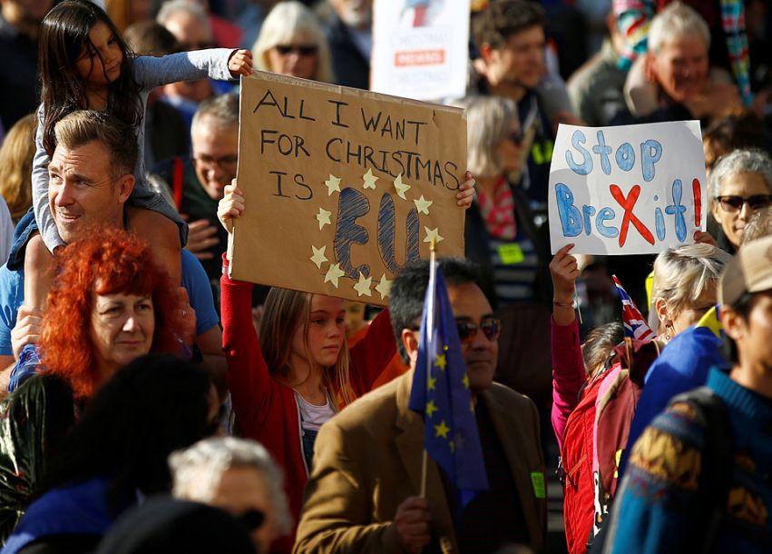 示威者揮舞歐盟旗幟及英國國旗,有人高舉標語牌。(圖片來源:路透社)