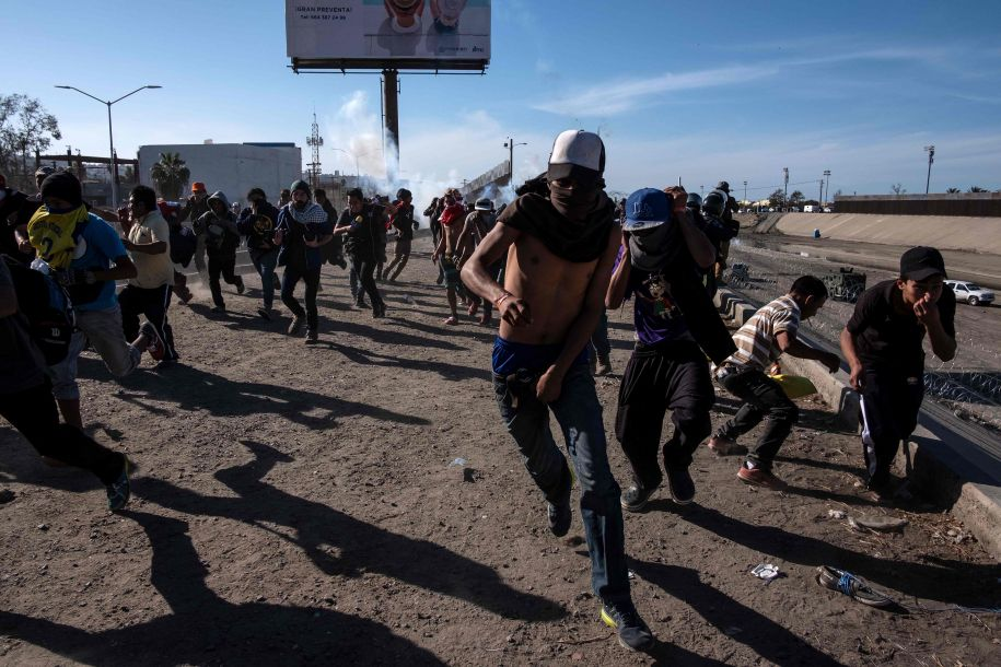 据美国《华盛顿邮报》网站11月25日报道,美国当局向冲击边境围栏的中美洲移民大军发射催泪瓦斯,并关闭了圣迭戈地区的主要入境口岸。该口岸是美墨边境最繁忙关卡处的车辆和人行通道。美国边境巡逻人员25日向聚集在美墨边境的中美洲移民发射催泪瓦斯。(图片来源:法新社)56
