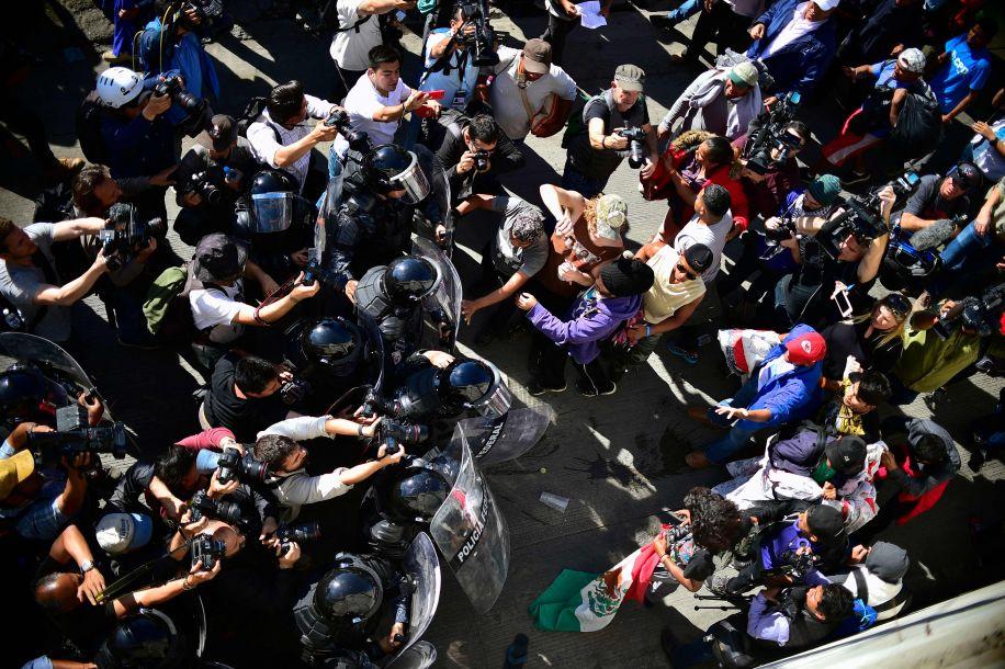 当移民人群接近入境口岸时,墨西哥防暴警察挡住了他们的去路,并使用路障关闭了通往一座行人天桥的通道。(图片来源:法新社)