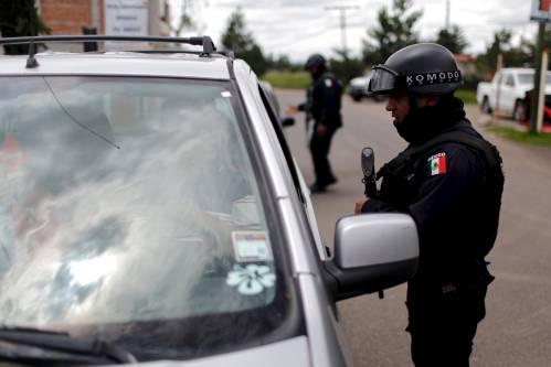 2015年7月,墨西哥警察在某联邦监狱附近的一处检查站检查过往车辆。 (新华社路透)