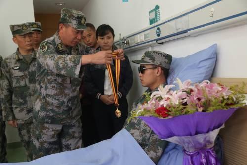 11月24日,南部战区陆军云南扫雷大队在病房内为杜富国举行颁授一等功证书证章仪式,大队领导为他佩戴军功章。(新华社)