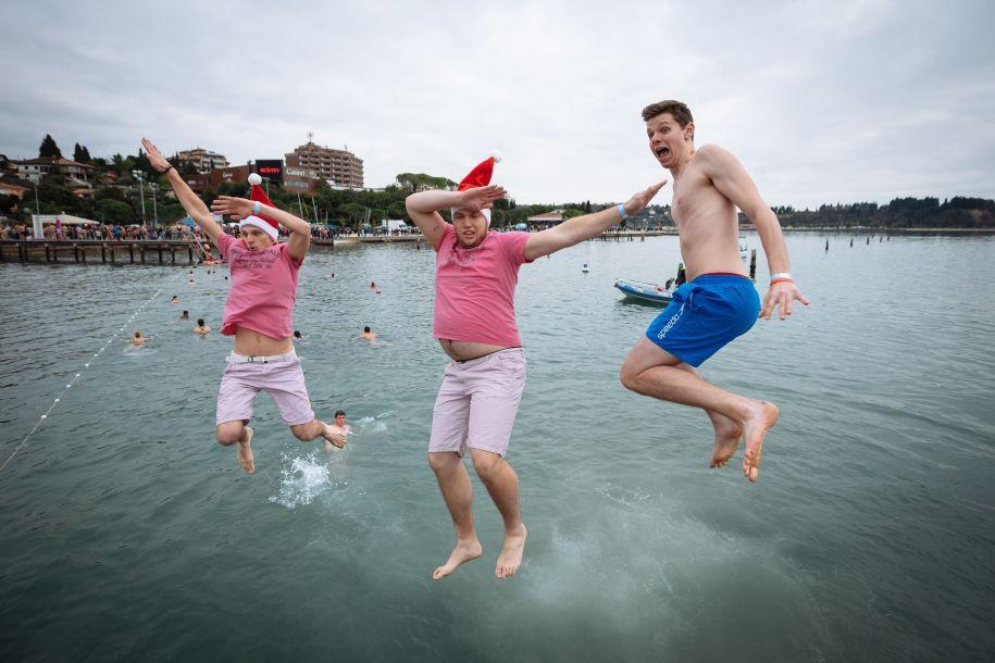 1月1日,在斯洛文尼亚波尔托罗日的亚得里亚海边,人们参加迎新年冬泳活动时跳入海里。新华社/法新
