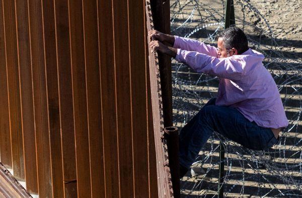 一名墨西哥移民试图从墨西哥蒂华纳一侧翻越边境围栏到美国圣迭戈境内(法新社)