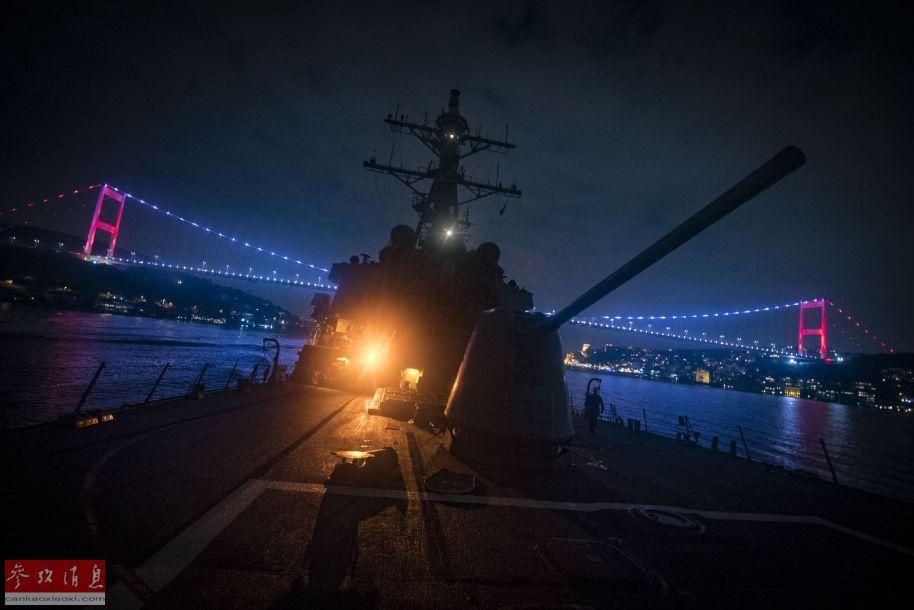 """从舰艏向艏楼方向拍摄的夜景照片,背景为海峡大桥,可见""""库克""""号的127毫米舰炮特写。"""
