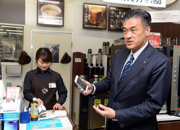 在日本东京的一家罗森便利店,罗森集团董事长兼首席执行官玉塚元一(右)体验使用支付宝结账。