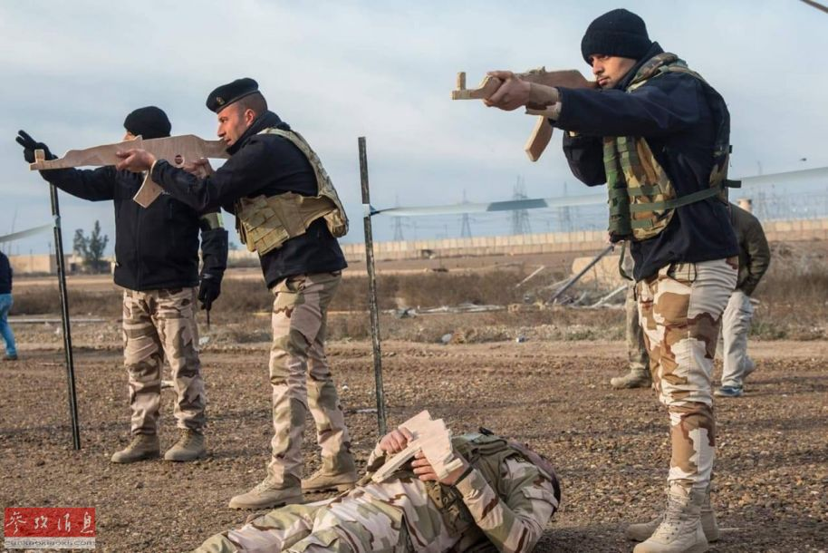 伊政府军士兵使用AK-47木模演练据枪,地上还有一位模拟中弹倒地的士兵。