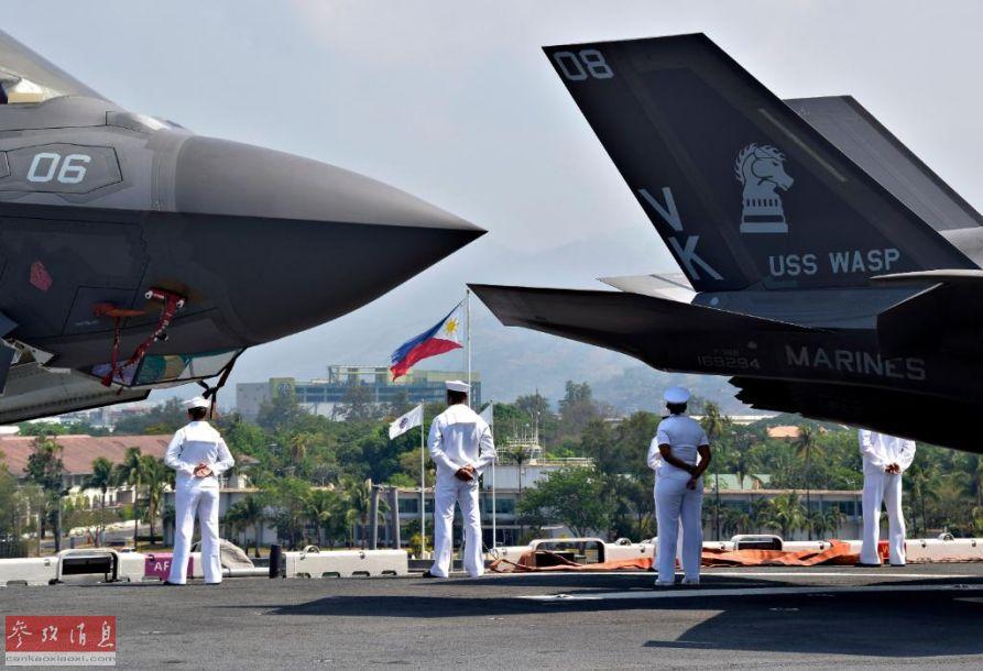 """图为美海军水兵在""""黄蜂""""号甲板上进行列队站坡仪式,可见F-35B的垂尾上的VMFA-121""""绿骑士""""中队徽标。"""