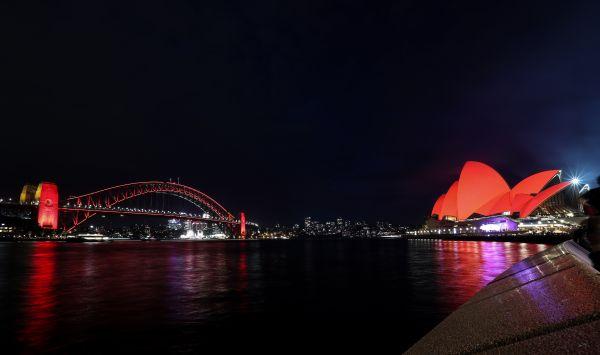 2月4日,澳大利亚悉尼的悉尼歌剧院和海港大桥同时点亮象征吉祥的红色照明,庆祝中国农历新年。(新华社)
