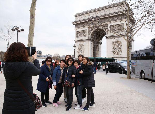 15-1、中国游客在法国巴黎凯旋门前合影(新华社记者高静 摄)
