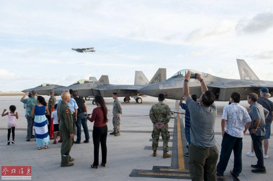 安德森基地美军官兵及军属参观F-22战机,背景可见一架B-52H战略轰炸机准备降落。
