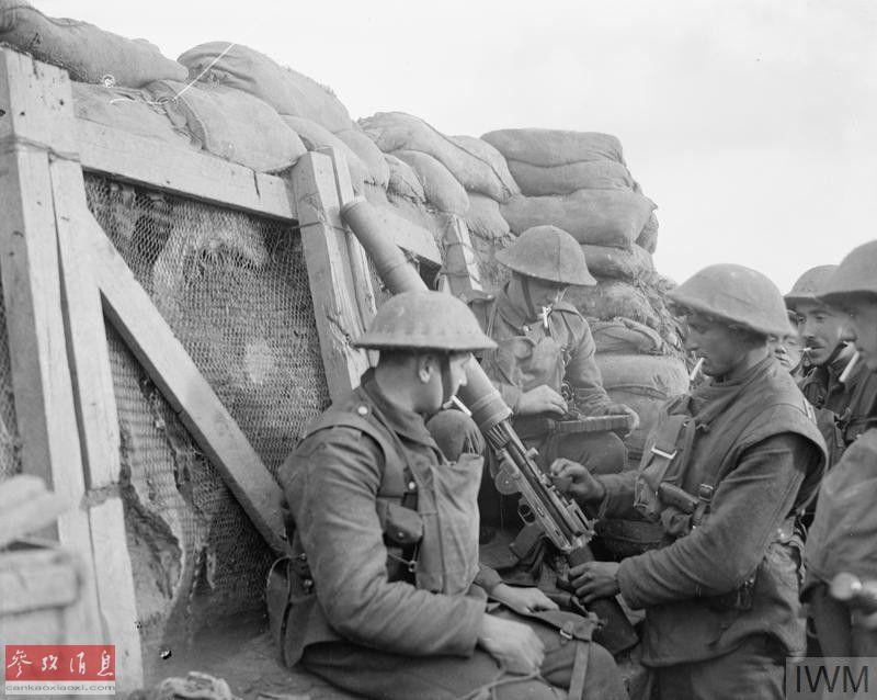 一名英军士兵在堑壕中擦拭刘易斯机枪,另一名士兵在为弹盘加装弹药。
