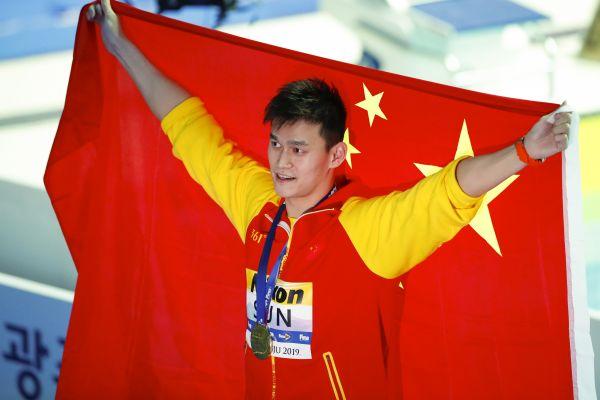 1.孙杨在颁奖仪式上身披国旗庆祝。(新华社)