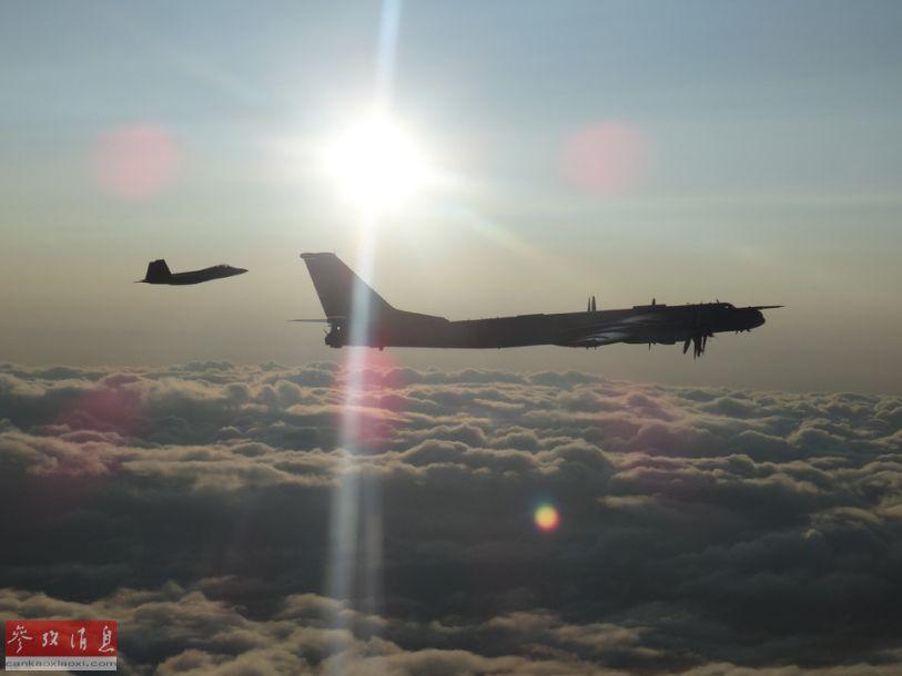 图为伴飞的加拿大空军战机拍摄的美军F-22与俄军图-95编队合影照。