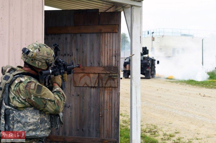 """在美军""""悍马""""车队遭""""伏击""""后,一名美军士兵向""""敌军""""开枪反击。"""