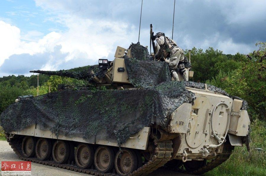 """一名""""敌军""""爬上美军M2""""布莱德利""""步战车,并向车内投掷""""手榴弹""""。"""
