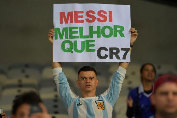 """一名阿根廷队的球迷在6月份对阵巴拉圭的美洲杯比赛开始时高举写有""""梅西比C罗更好""""的标语"""