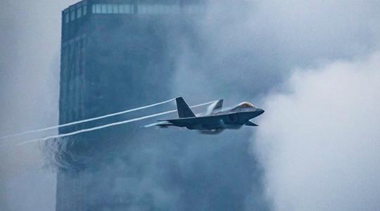 穿云破雾!美军F-22在楼群间秀特技飞行