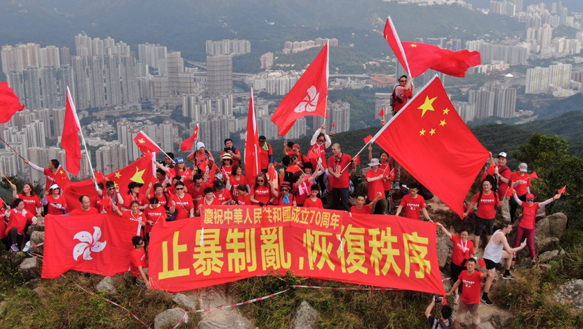 百余名香港市民爬上狮子山顶挥舞国旗、区旗