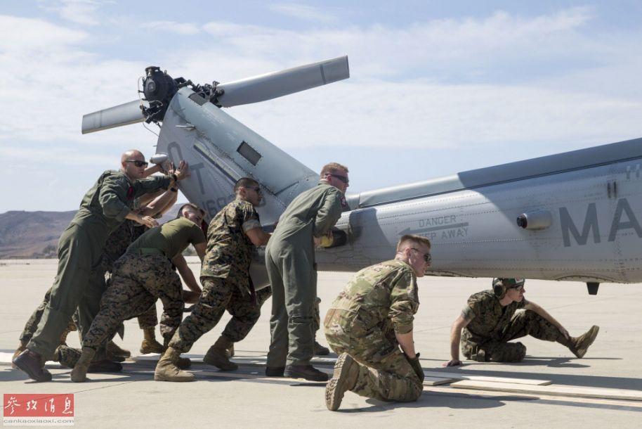 美海军陆战队员正猛推UH-1Y直升机的机尾,较为考验团队协作和个人体力。