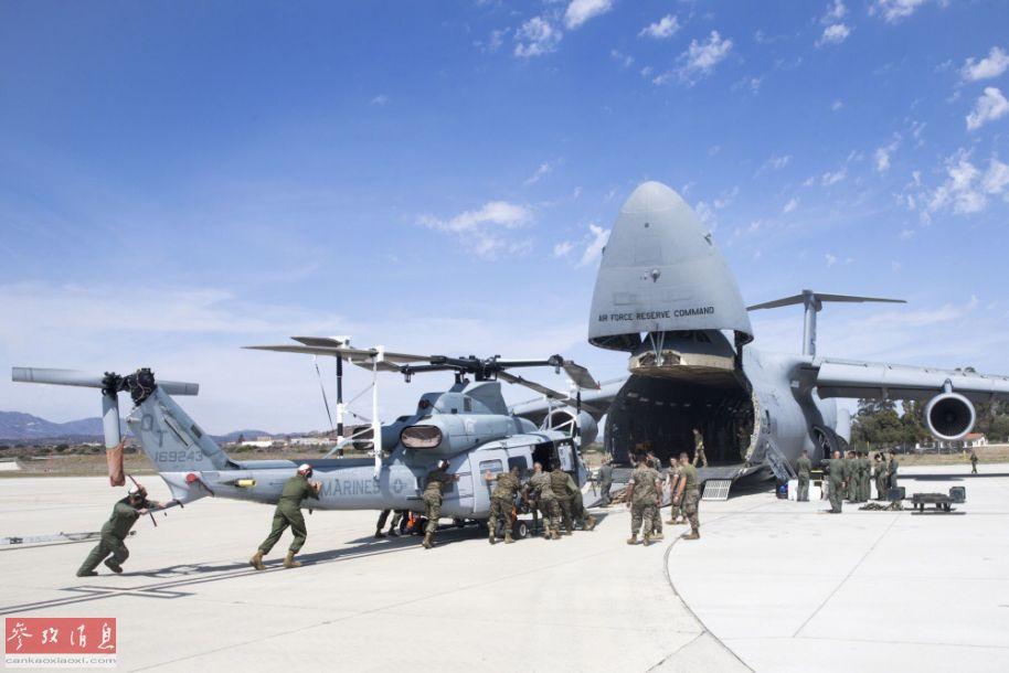 """9月16日,美国加州彭德尔顿兵营航空站,美海军陆战队员正在以人力推动方式将一架UH-1Y""""毒液""""运输直升机推入一架美空军的C-5M""""超级银河""""战略运输机的货舱内。图为美海军陆战队员正在以人力推动方式将一架UH-1Y""""毒液""""运输直升机推入一架美空军的C-5M""""超级银河""""战略运输机的货舱内。11"""
