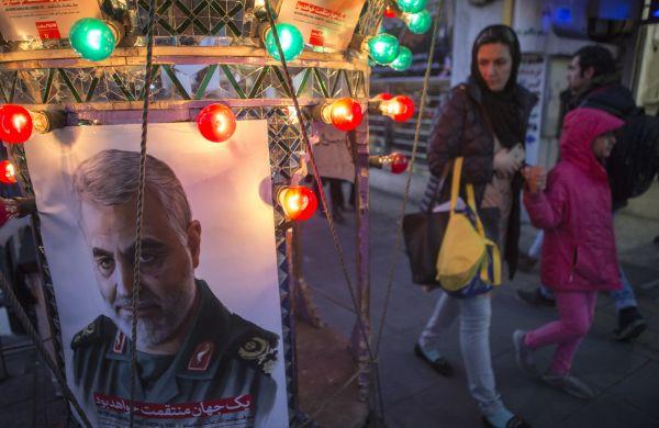 """1月5日,在伊朗首都德黑兰,人们走过悼念伊朗伊斯兰革命卫队下属""""圣城旅""""指挥官苏莱曼尼的海报。新华社发(艾哈迈德·哈拉比萨斯摄)"""