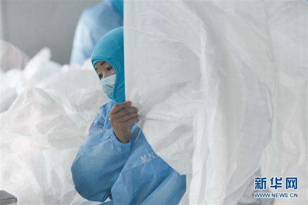 2月5日,在安徽莫尼克医用材料有限公司,工作人员在赶制防护服。新华社记者张端摄
