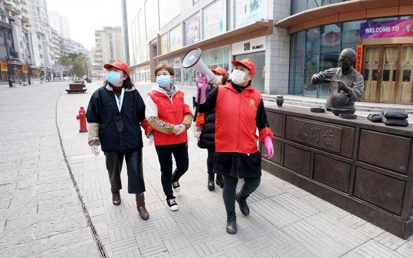 2月13日,武汉市汉正街石码社区工作人员在步行街上向居民宣传防疫知识。(王毓国 摄)