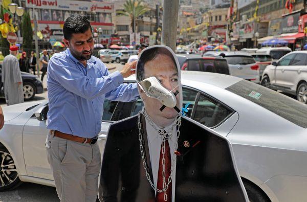 5月14日,一名巴勒斯坦抗议者在约旦河西岸城市纳布卢斯把一只鞋系在蓬佩奥的画像上。(法新社)