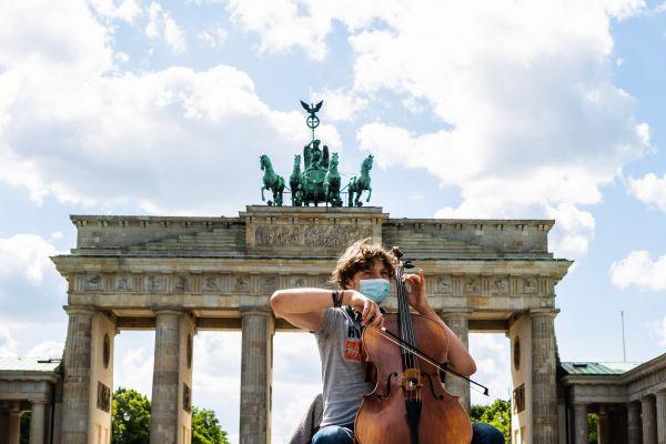 5月26日,在德国首都柏林,一名艺人在勃兰登堡门前演奏。新华社发