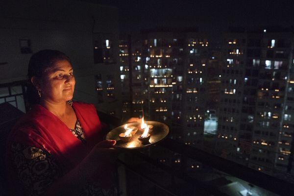 4月5日,在印度新德里,一名女子在阳台点亮烛光,支持抗疫。(新华社)