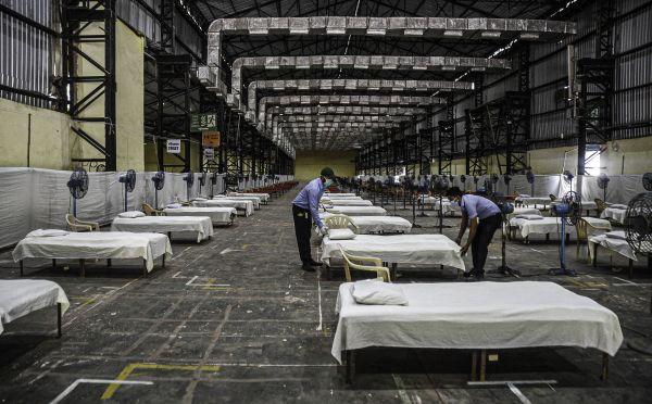 4月27日,在印度孟买一处政府设置的临时集中隔离点,工作人员在整理卧具。(新华社)