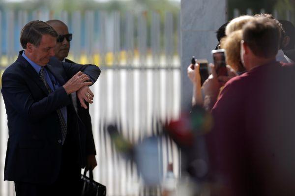 3月16日,在巴西巴西利亚,巴西总统博索纳罗(左)离开总统官邸。(新华社 路透)