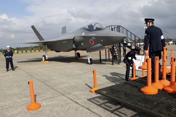 这是在日本东京以北的茨城县百里基地,日本航空自卫队人员在F-35战斗机模型旁设置警戒线的资料照片(2014年10月26日摄)。新华社/美联