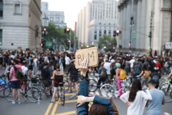 """2020年6月30日,一名抗议者在美国纽约市政厅附近手举写有""""黑人的命也重要""""缩写的标语参加抗议活动。(新华社)"""